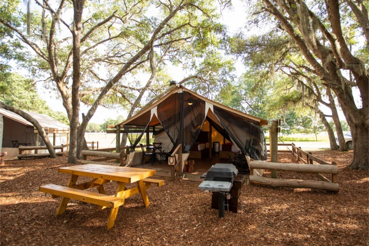 Picnic tables set up in front of Westgate River Ranch's glamping tents