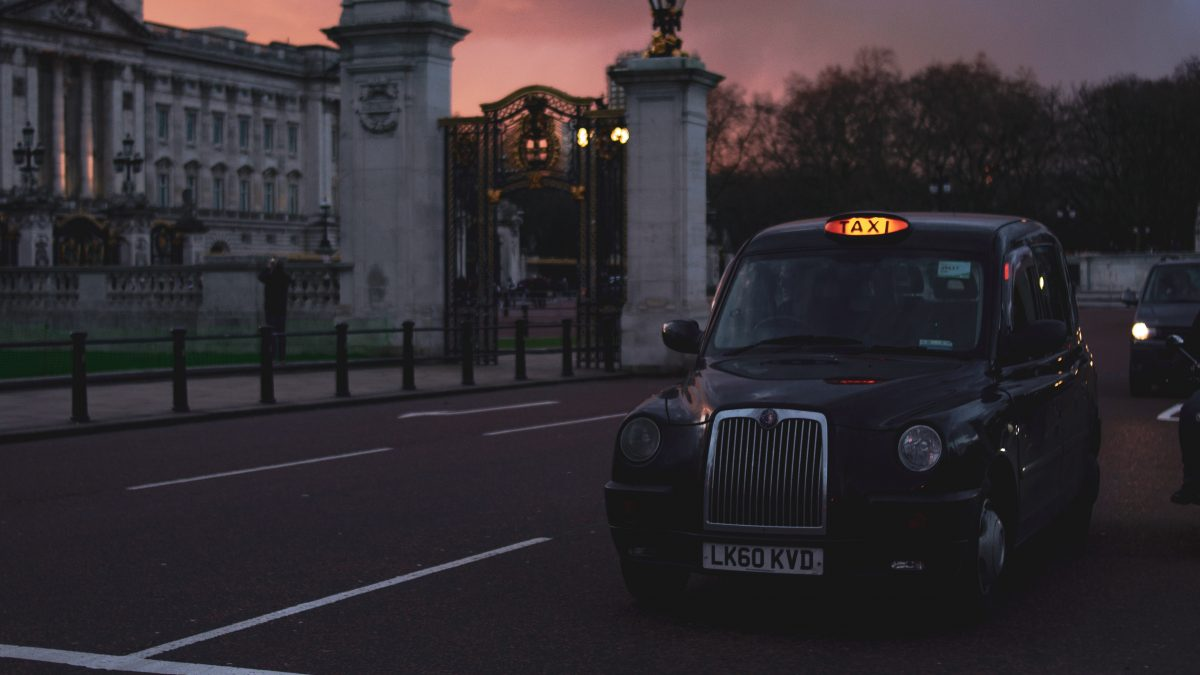 A black taxi plies London's roads at sunset