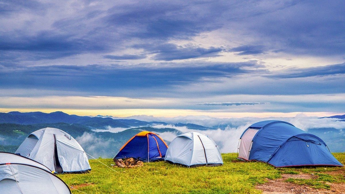 Clouds surround pitched tents on high ground