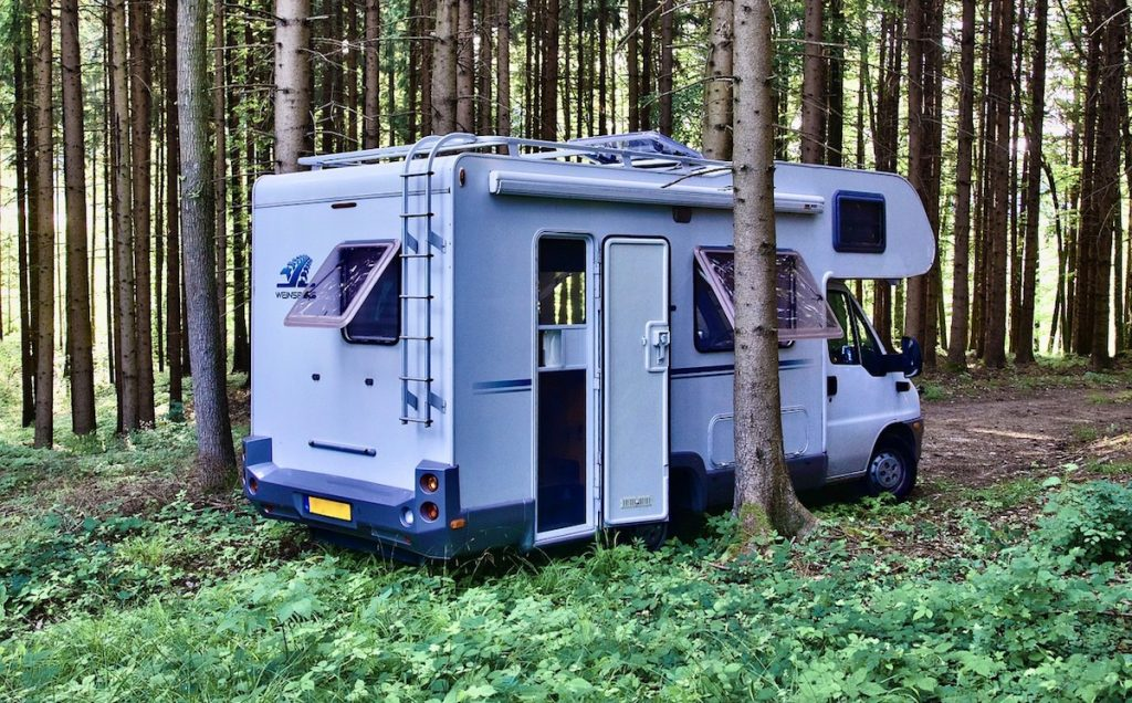 A campervan parked in the woods