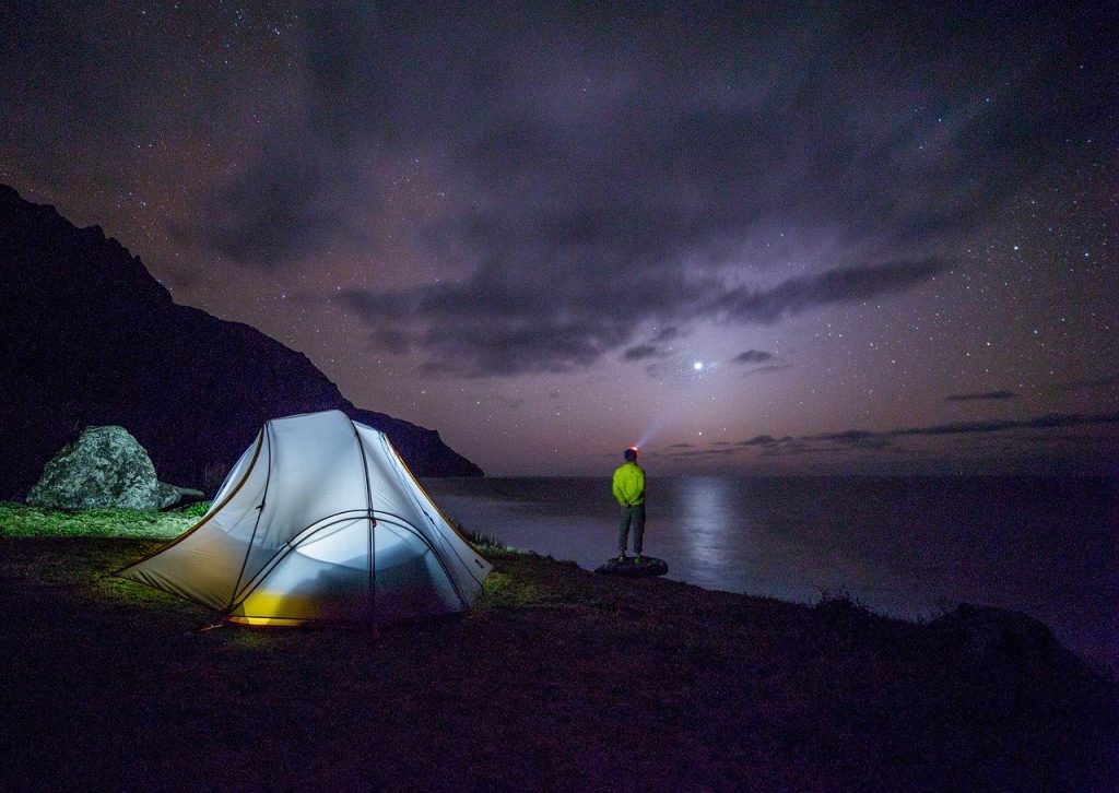 Well-lit camping tent against a starry night