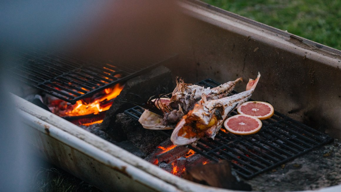 Two open-bellied fish being grilled with cut citrus fruit also grilling next to the fish and the grill on top of a fire lit by coal within a grilling basin