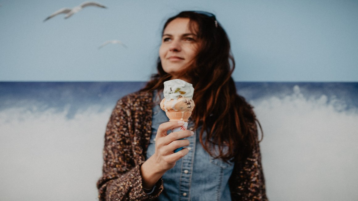 Photo of a woman with long brown hair wearing a denim polo and a brown patterned cardigan holding an ice cream cone with white and peach scoops melting with a painted blue background of a sky with birds and a blue ocean