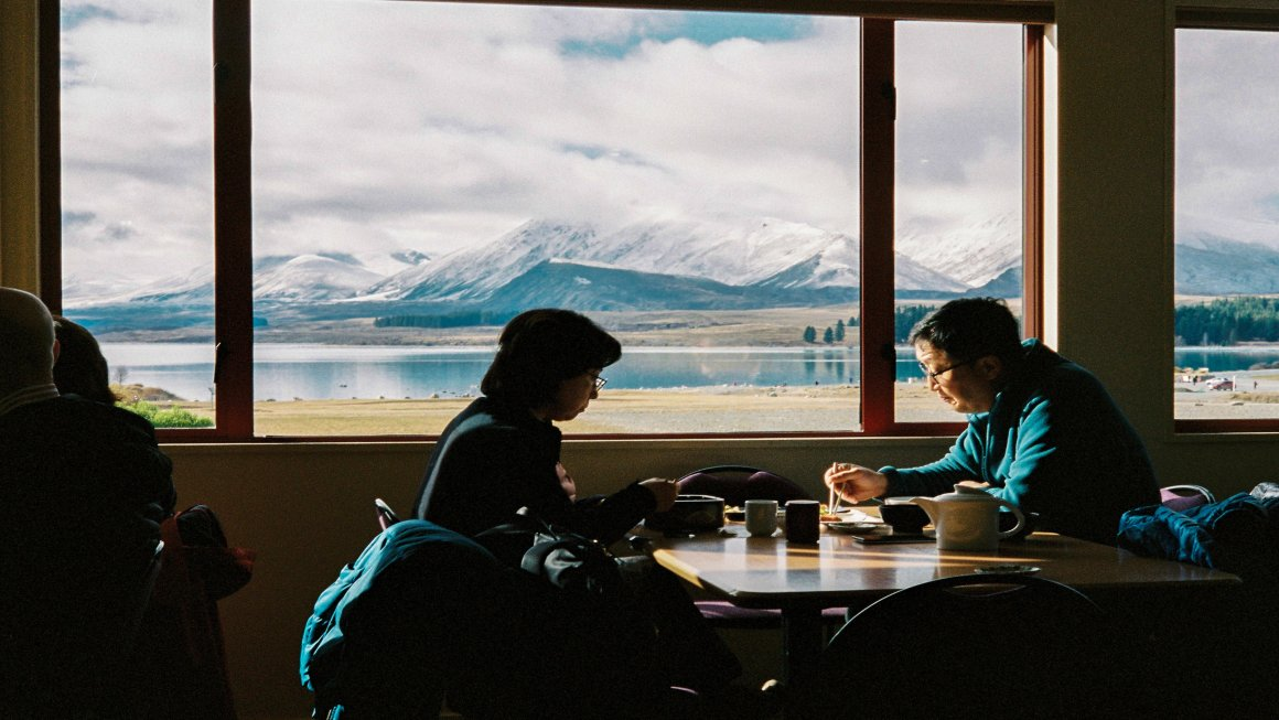 A middle-aged couple enjoying their New Zealand food by the large window showcasing Lake Tekapo, New Zealand and mountains in the distance and a sky covered with clouds and a blue sky barely visible behind the clouds
