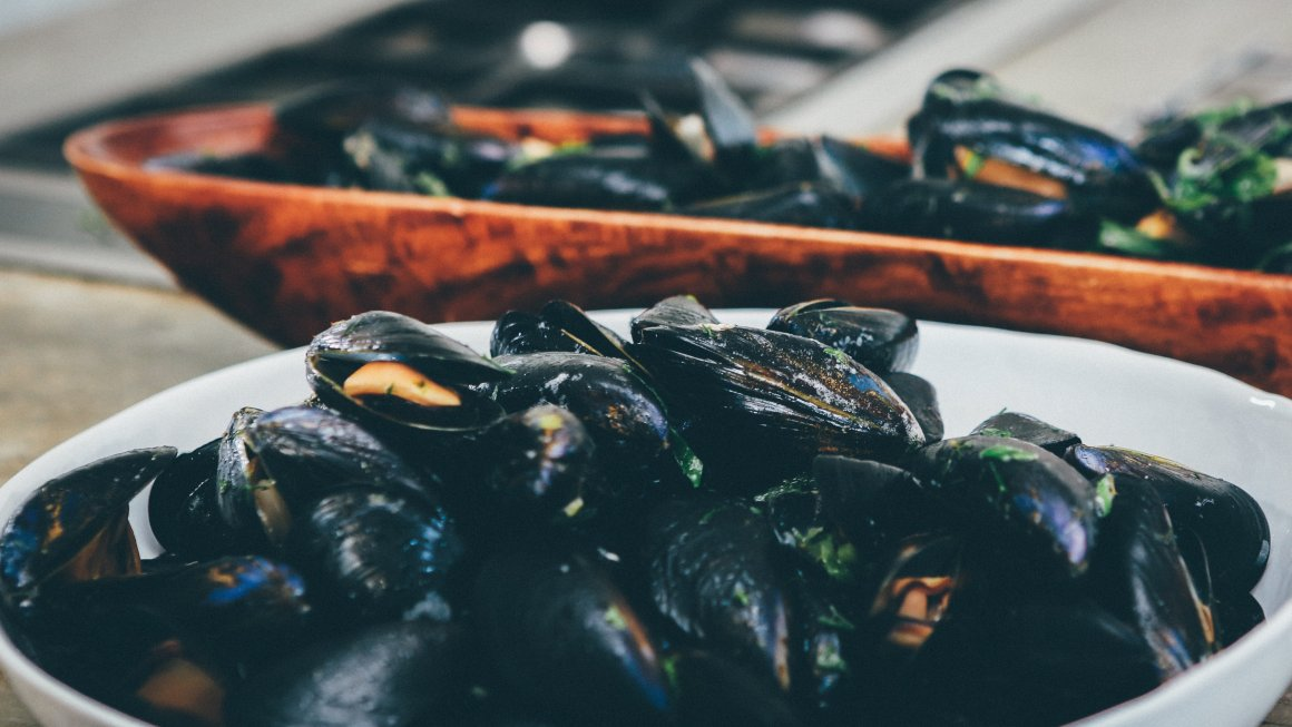 Photos of mussels in a white ceramic bowl and a wooden brown bowl on a table