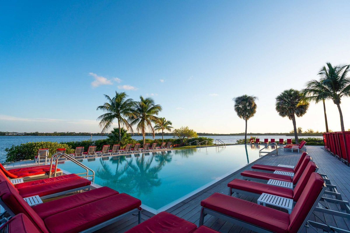 Red lounge chairs surround the pool overlooking St. Lucie River in Club Med Sandpiper Bay, Port St. Lucie. Florida