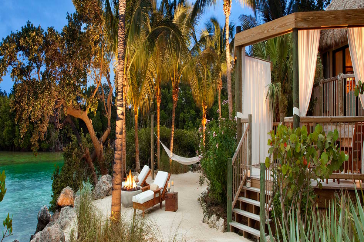 Two lounge chairs, a hammock, and a fire pit sit outside a bungalow amidst lush vegetation and water in Little Palm Island Resort & Spa, Little Torch Key, Florida
