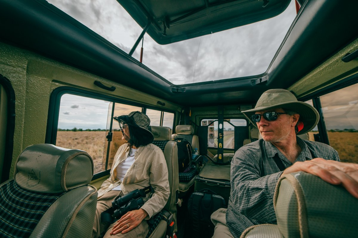 A man and a woman sitting inside a safari jeep