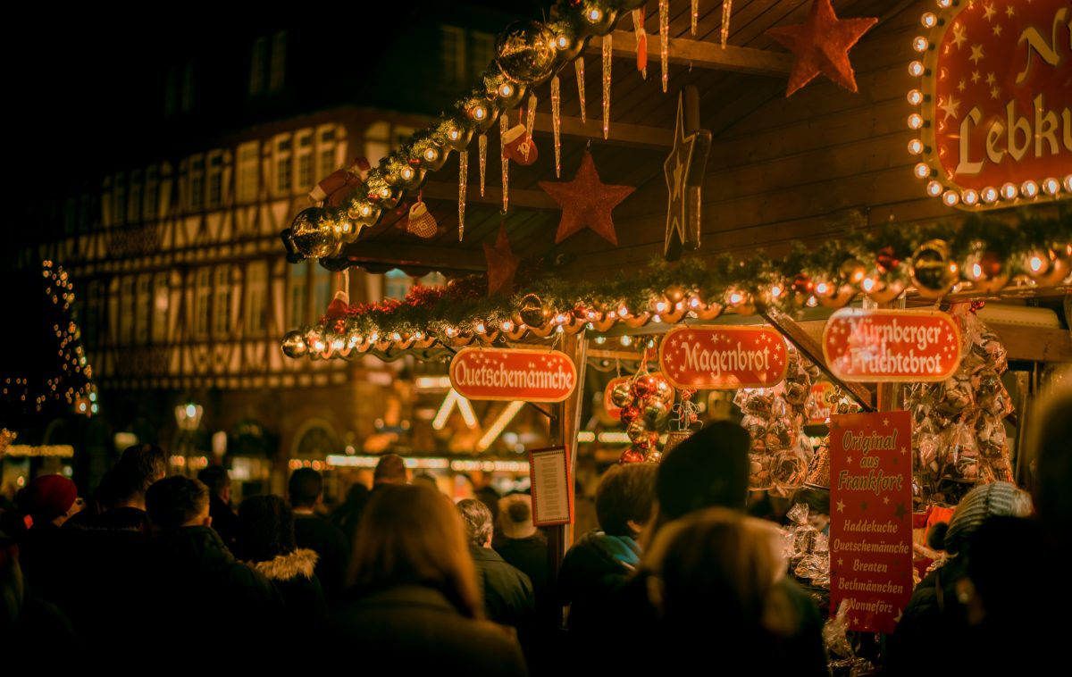 Shoppers standing by a beautifully lit Christmas stand