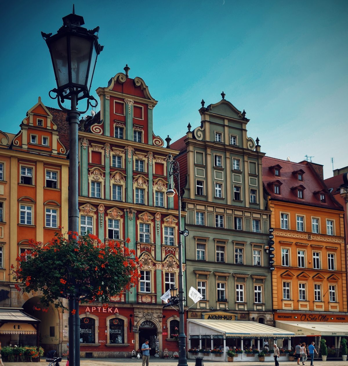 People walking in front of multicolored buildings in Wroclaw, Poland