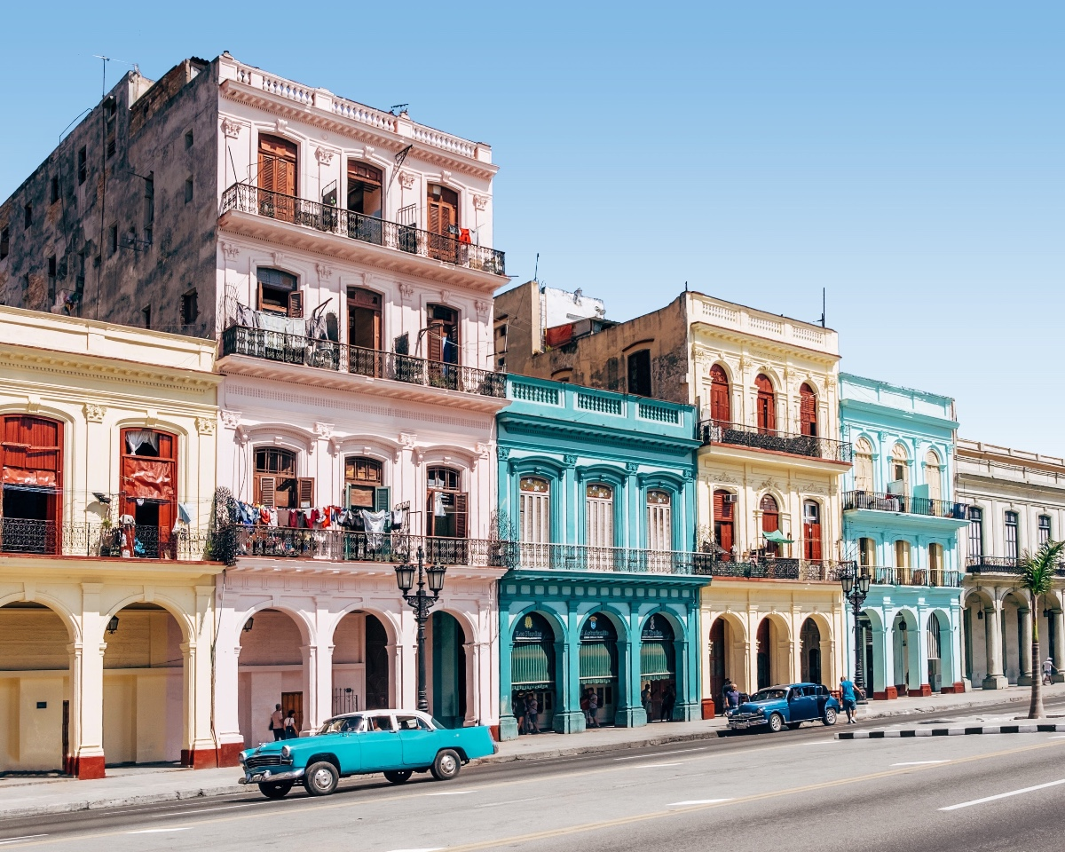 Photo of colorful Cuban buildings with big archways in front Of them and a bright blue car in front of the pink building and a dark blue car in front of the cream colored building, with the road empty and a clear afternoon sky
